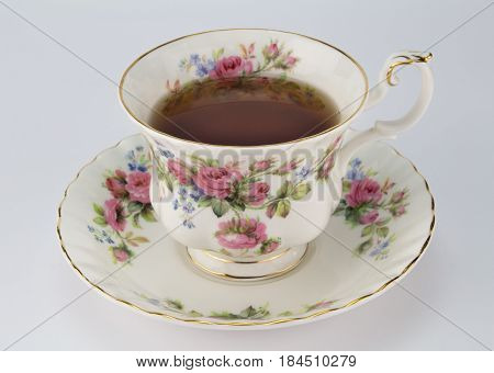 Full antique teacup and saucer with rose and gold decoration isolated on white