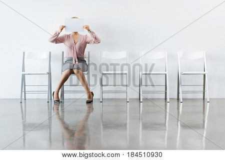 Businesswoman Covering Face With Paper