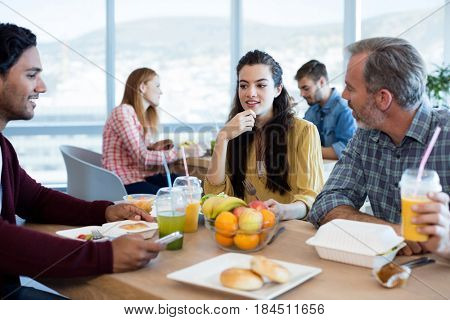 Creative business team discussing while having meal in office