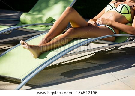 Woman relaxing on lounge chair at poolside on a sunny day