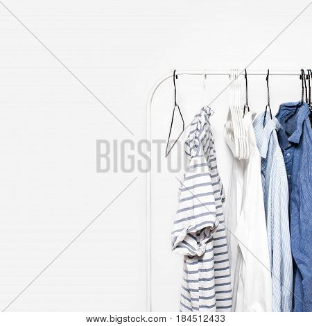Stripped Clothes on a Rack over white Wall Background close up with copyspace. Blue White
