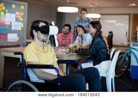 Physically disabled man on wheelchair using VR headset in office