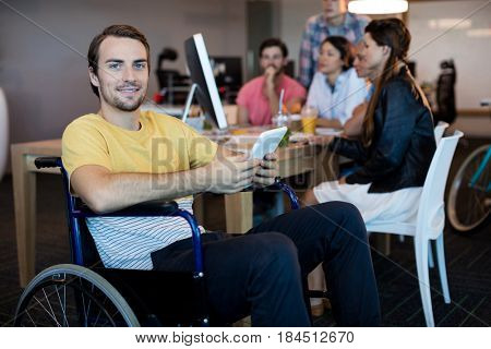 Portrait of physically disabled man on wheelchair using tablet in office