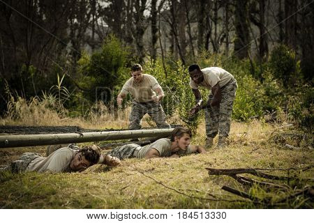 Soldiers crawling under the net during obstacle course in boot camp