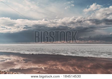 Scenery view of frozen river during ice drift on springtime with dramatic dark sky and clouds having reflections in melt water on evening in Novosibirsk Russia