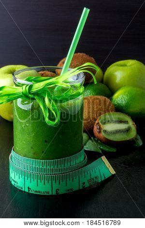 Green Smoothie Near Centimeter And  Ingredients For It On Black Wooden Background. Diet. Detox. Heal