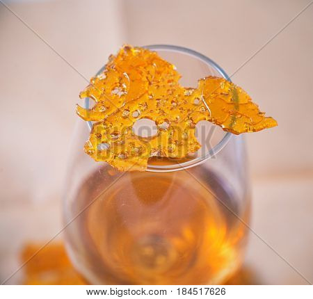 Abstract detail of cannabis oil concentrate aka shatter isolated against white background