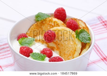 bowl of american pancakes with white yogurt and fresh raspberries on on checkered dishtowel - close up