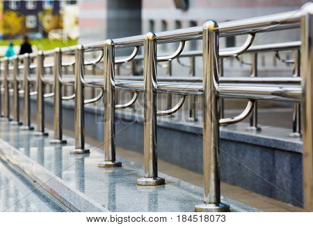 Chromium metal fence with handrail. Metal railings. Shallow depth of field. Selective focus.