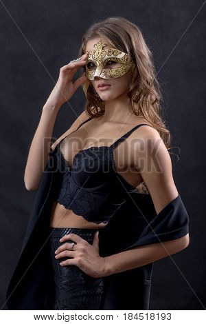 beautiful woman in mask undressing on black background