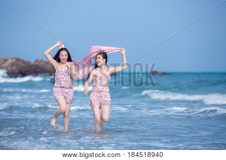 Two Asian woman run happily together on the beach.