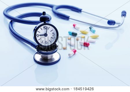 Time for health checkup with stethoscope and pills on blue background