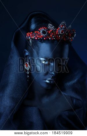 Jewelry industry. Fashion portrait of a beautiful young woman with perfect black skin wearing diadem with precious stones and black veil. Jewelry and bijouterie. Body painting project.