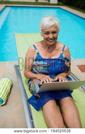 Portrait of senior woman using laptop on lounge chair at poolside