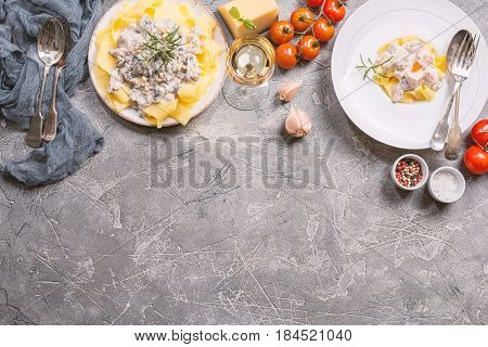 Fresh Tagliatelle pasta with Salmon and mushrooms in a cream sauce in white plate on gray background top view with copy space