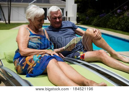 Senior couple looking at digital tablet on lounge chair near poolside