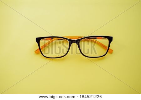 glasses lie . Black orange glasses . Office workplace with glasses on wood table. Glasses with orange rim. Orange Case for storage points.