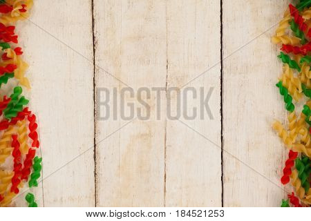 Close-up of tri-colored rotini pasta on wooden background