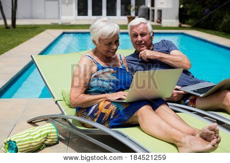 Senior couple using laptop on lounge chair at poolside