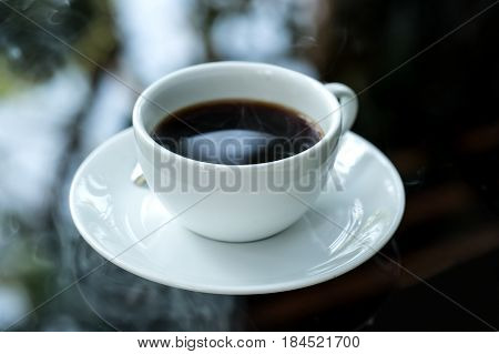 Americano coffee in white cup on glass table.