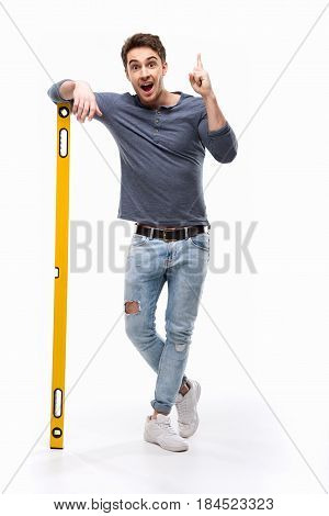 Handsome Man Pointing Up And Holding Building Level Isolated On White, Handyman Tools Concept