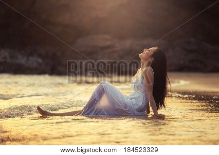 Asian girl sitting on a tropical beach by the sea to enjoy the sea breeze happily near the sunset.