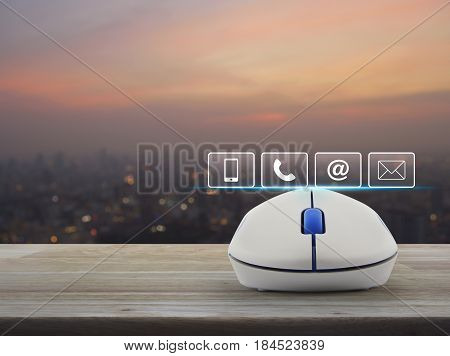 Telephone mobile phone at and email buttons with wireless computer mouse on wooden table over blur of cityscape on warm light sundown Customer support concept