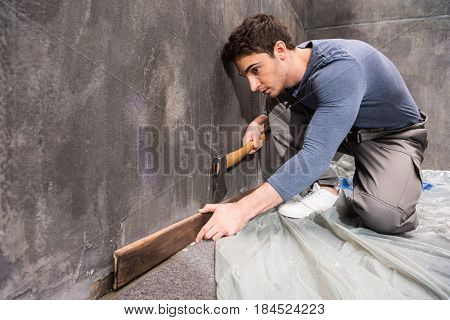 Professional Young Handyman With Axe Repairing Floor, Renovation Concept