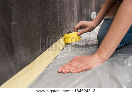 Close-up Partial View Of Young Woman Kneeling And Working With Tape, Renovation Concept