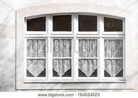 Old closed windows with white lace curtains