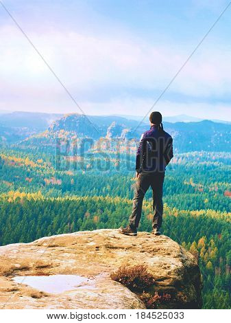 Hiker On Rock End Above Valley. Man Watch Over Misty And Autumnal Morning Valley To Bright Morning S