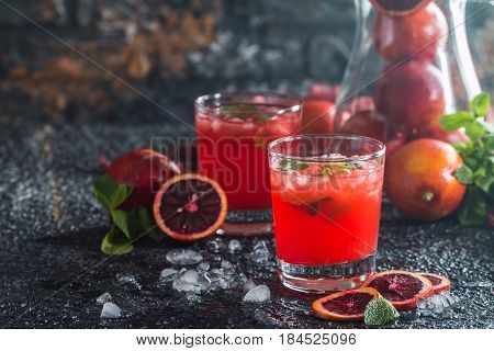 Glasses of fresh blood orange juice with mint on black background