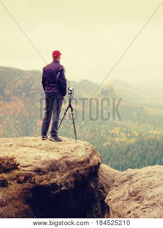 Tall Adult  Photographer Prepare Camera For Taking Picture Of Fall  Mountains.