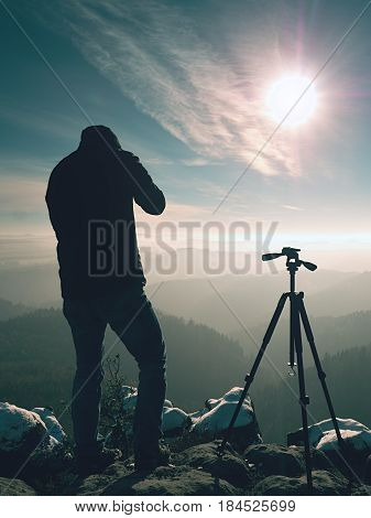 Professional nature photographer do work on snowy cliff. Man takes photos with mirror camera on peak of rock. Dreamy fogy landscape spring orange pink misty sunrise.