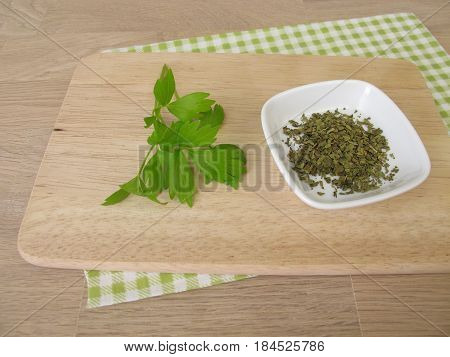 Dried and fresh lovage on wooden board