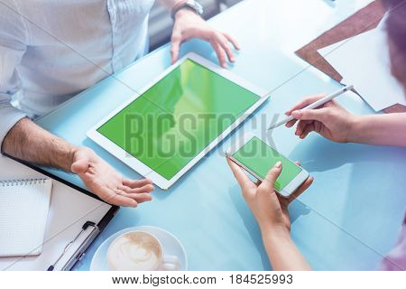 Man and woman discussing a project with smartphone and tablet. Clipping path included.