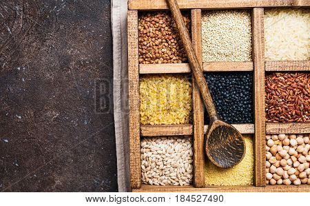 assortment of different cereals and seeds in a box on dark brown background, top view
