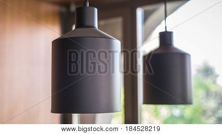 Two metal chandeliers in the interior on the background of the window