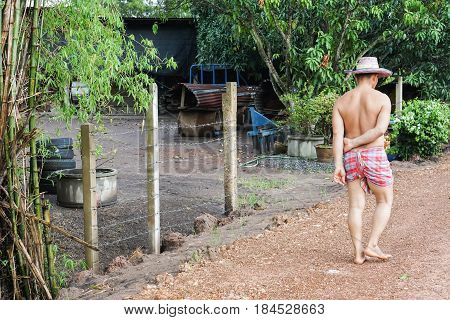 farmer wearing loincloth with hat walk barefoot on dirt road to his house