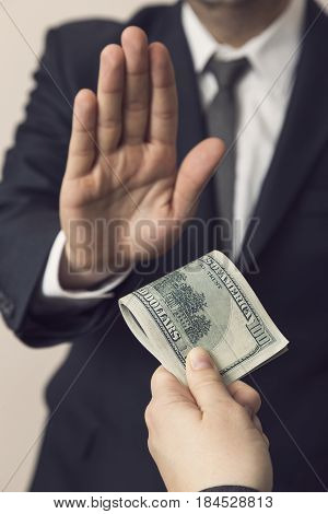 Detail of an honest businessman refusing a bribe money. Focus on the thumb of the bribe giver