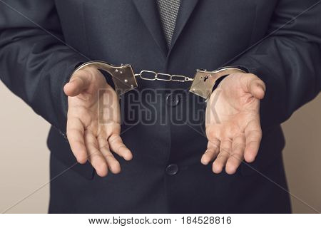 Businessman in a suit with handcuffs arrested. Selective focus