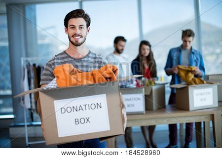 Portrait of smiling man holding a donation box in office