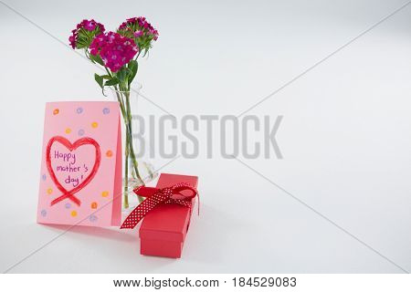 Happy mothers day greetings with gift box and flower vase on white background