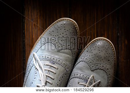 Grey oxford shoes on wooden background. Top view