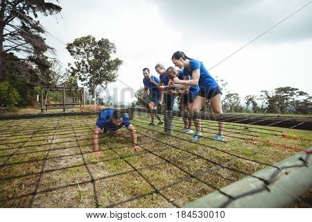 Fit man crawling under the net during obstacle course while fit people cheering in bootcamp