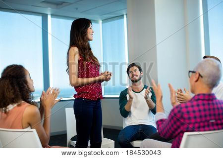 Creative business team applauding their colleague at office