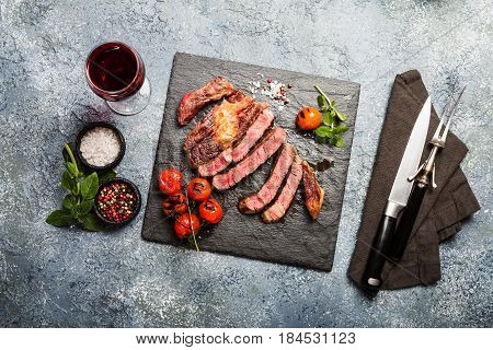 Sliced grilled Medium rare beef steak Ribeye with seasonings and red wine on slate cutting board, top view