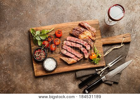 Sliced grilled Medium rare beef steak Ribeye with seasonings and red wine on wooden cutting board, top view