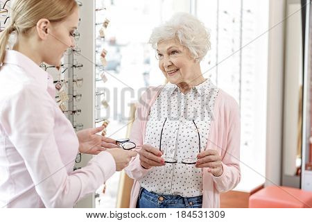 Happy old lady is standing beside consultant in optic shop. They are holding glasses. She glancing with smile. Portrait