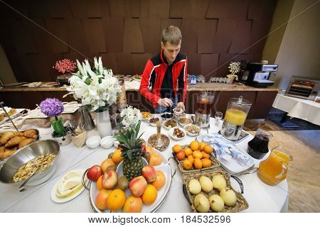 Man takes nuts in buffet in hotel during breakfast, many fruits and other food are on table